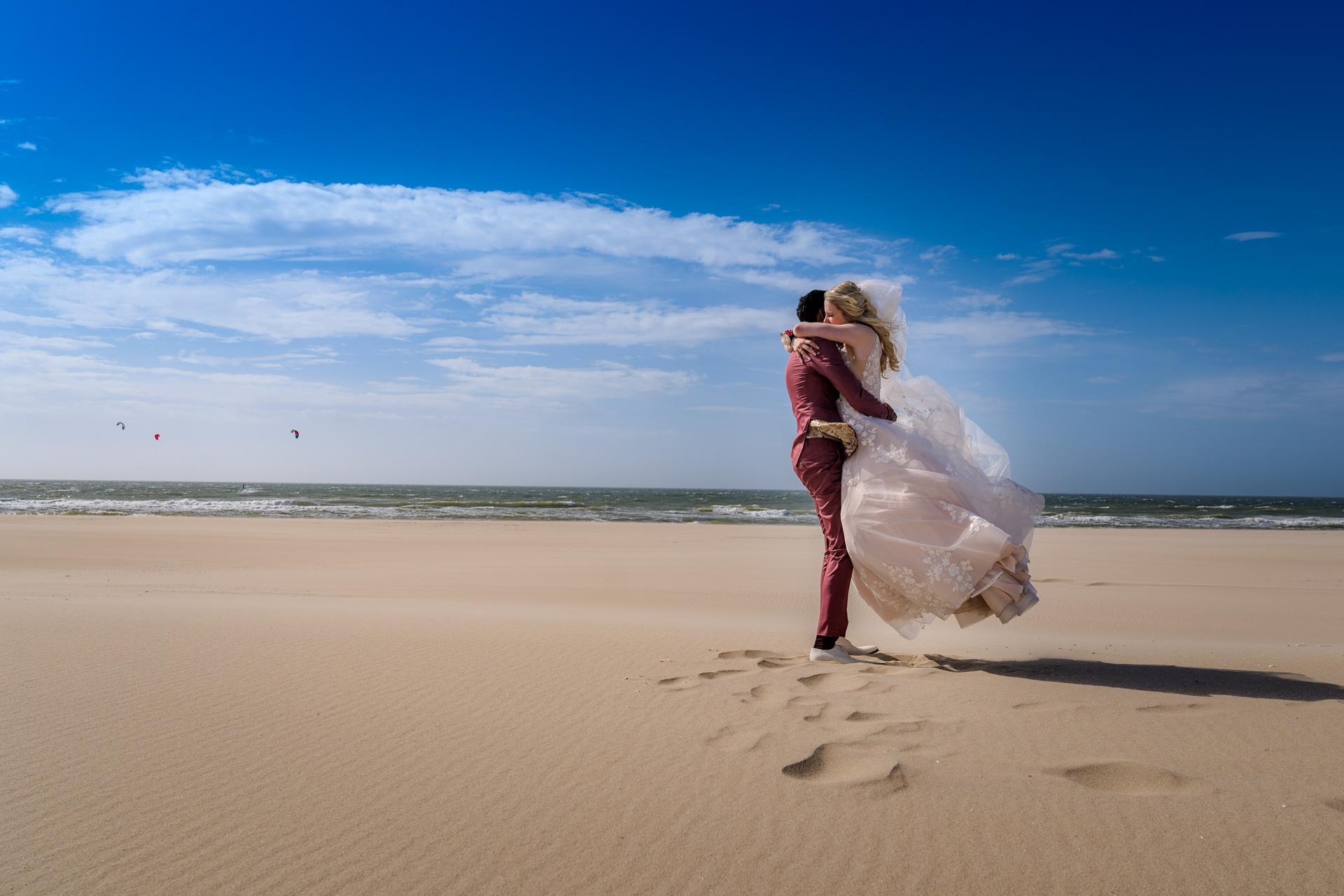 Bruiloft Kijkduin strand optillen bruid
