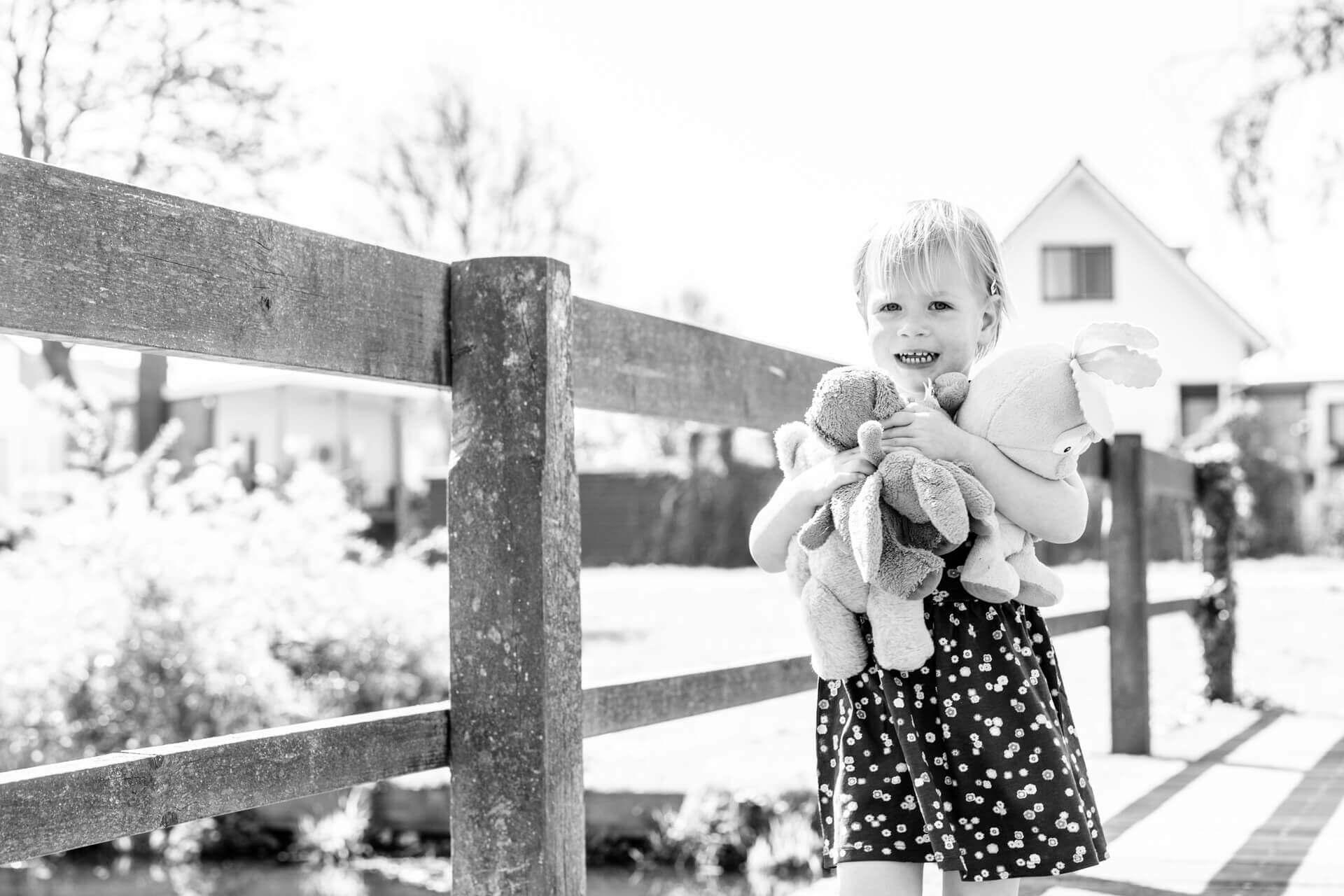 Fotoshoot Haarlem kind met knuffels en meneer wortel zwart-wit door kinderfotograaf Grietje Mesman