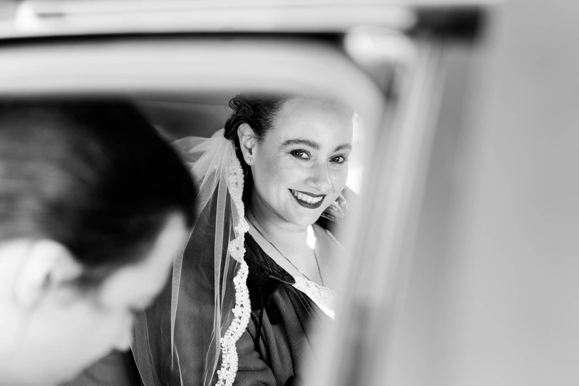 Bruid in trouwauto in zwart-wit